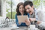 Two friends using digital tablet in the sidewalk cafe, Bavaria, Germany
