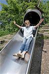 Boy sliding on slide in playground, Munich, Bavaria, Germany