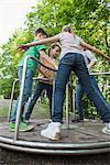 Children having fun on a carousel in playground, Munich, Bavaria, Germany