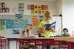 Schoolboy reading a book in classroom, Munich, Bavaria, Germany