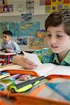 Schoolboy reading a message in classroom, Munich, Bavaria, Germany