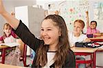 School children with raised hands in classroom, Munich, Bavaria, Germany