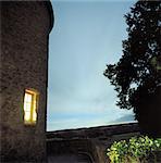 Lit window of stone house