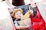 Boy riding in shopping cart