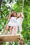 Smiling girls standing on tree swing