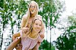 Young girl giving sister a piggyback ride