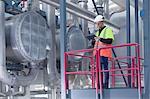 Engineer using digital tablet on access platform in geothermal power station