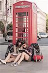 Two women backpackers sitting on sidewalk using digital tablet, London, UK