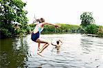 Teenage boy and sister jumping into lake