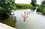 Teenage boy somersaulting into rural lake