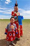 Woman and child in traditional dress (deel), silver bowl for milk greeting, near ger, Gobi desert, Bulgan, Omnogov, Mongolia, Central Asia, Asia