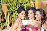 Three adult sisters wearing bikini tops posing for smartphone selfie in garden