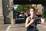 Mid adult woman, running, wearing earphones, outdoors
