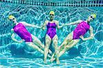 Three female swimmers, underwater, holding hands