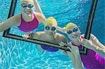 Three female swimmers, underwater, looking through frame
