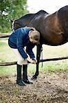 Girl checking horses hoof