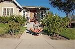 Boy skateboarding down garden path