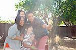 Family with boy posing for smartphone selfie in sunlit garden
