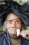 India, Arunachal Pradesh, Ziro Valley, near New Ziro. At Lempia a pipe smoking, rain hat wearing villager belonging to the Apatani tribe participates in traditional shamanic rituals.