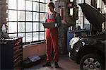 Mechanic using laptop by window at garage