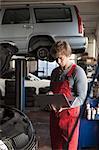 Mid adult mechanic using laptop at garage