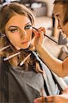 Make-up artist applying eyeliner on fashion model