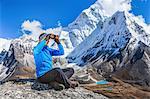 Young woman using binoculars in Himalayas