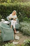 Blond woman sitting in a wicker chair in a garden, reading.