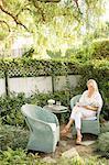 Blond woman sitting in a wicker chair in a garden.