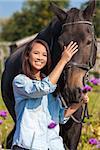 Beautiful happy Asian Eurasian young woman or girl wearing denim shirt, smiling and leading her horse in sunshine