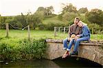 Romantic young couple sitting on river footbridge
