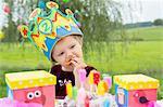Female toddler eating birthday cake in garden