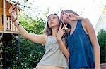 Two teenage girls posing for smartphone selfie in garden