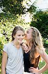 Two teenage girls whispering in garden