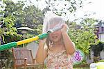 Girl with butterfly net over head in garden