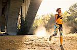 Jogger running under arch, Arroyo Seco Park, Pasadena, California, USA
