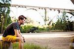 Jogger taking break, arch bridge in background, Arroyo Seco Park, Pasadena, California, USA