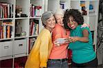 Portrait of three mature women, taking self portrait, using smartphone