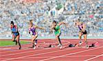 Four female athletes on athletics track, leaving starting blocks