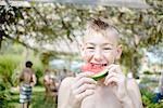 Boy enjoying watermelon at tomato eating festival
