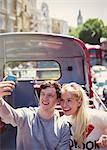 Couple taking selfie on double-decker bus in London