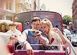 Couple taking selfie on double-decker bus, London, United Kingdom
