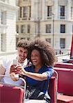Couple taking selfie on double-decker bus
