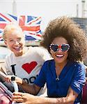 Portrait enthusiastic friends with British flag riding double-decker bus