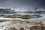 Snow covered mountain range behind craggy bay, Sund, Lofoten Islands, Norway