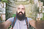 Bearded man posing against old brick wall, Garda, Italy