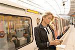 Business woman texting on platform, Underground station, London, UK