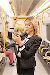Businesswoman texting on tube, London Underground, UK