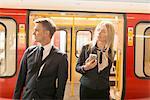 Businessman and businesswoman alighting train, London Underground, UK