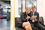 Businessman and businesswoman sharing digital tablet, London Underground, UK